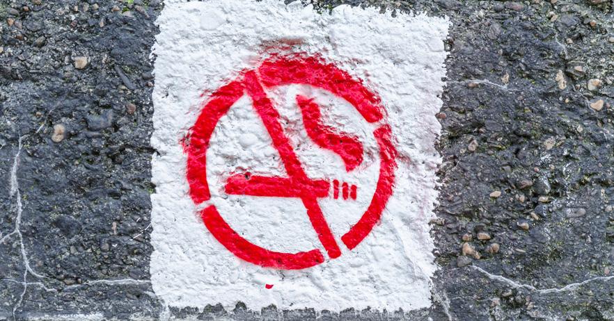 Graffiti smoking ban on an old concrete wall.