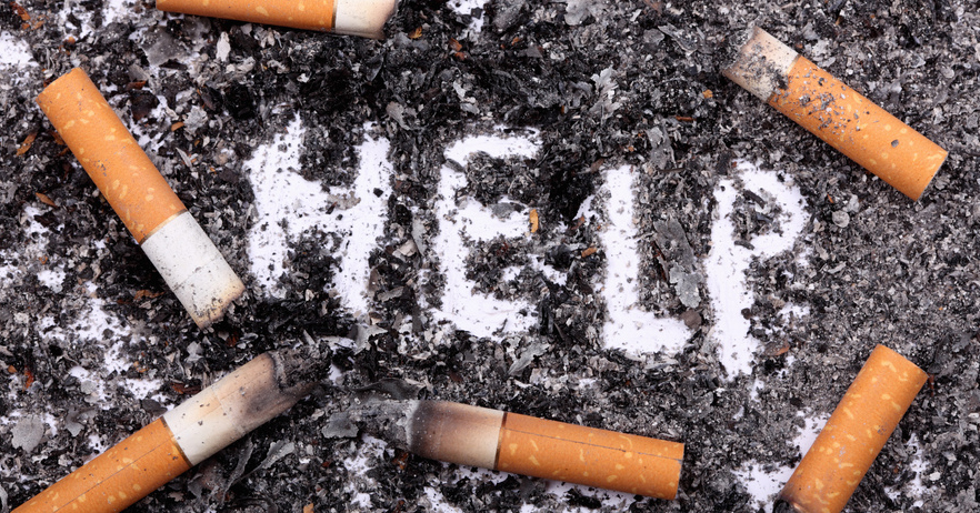 """Unhealthy habit. Cigarette butts on ash background with word: """"Help"""". Conceptual image. Close-up."""